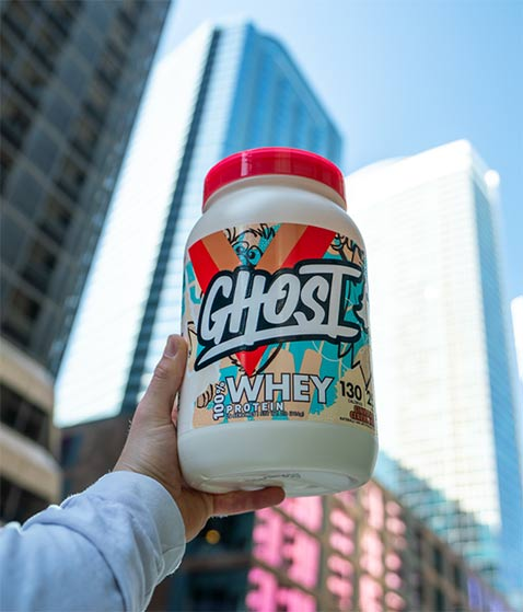 A man holding ghost whey protein